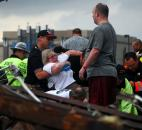 Emergency workers pull out a woman who was trapped in a building that was destroyed Monday after a tornado ripped through Moore, Okla. (Photo by The Associated Press)