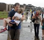Teachers carry children away from Briarwood Elementary school after a tornado destroyed the school in south Oklahoma City on Monday. (Photo by The Associated Press)