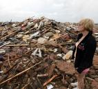 Resident Kim Schwab looks over her destroyed home Monday in south Oklahoma City. (Photo by The Associated Press)
