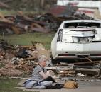 Kay James holds her cat as she sits in her driveway after her home was destroyed by the tornado that hit the area Monday. (Photo by The Associated Press)