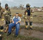 Oklahoma City firefighters check on the status of Gene Tripp as he sits in his rocking chair where his home once stood after being destroyed by a tornado that hit the area Monday. (Photo by The Associated Press)