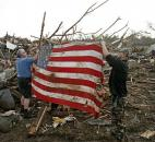 Clark Gardner, left, and another man place an American flag on debris in a neighborhood off of Telephone Road in Moore, Okla., after a tornado moved through the area Monday. (Photo by The Associated Press)