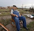 Gene Tripp sits in his rocking chair where his home once stood after being destroyed by a tornado hit Monday. (Photo by The Associated Press)