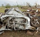 The remains of a car destroyed by a tornado. (Photo by The Associated Press)