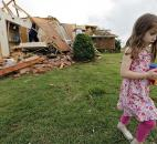 Magen Stanley, 5, walks away from her grandparents' destroyed home after a tornado hit the area Monday. (Photo by The Associated Press)