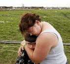 Rebekah Stuck hugs her son, Aiden Stuck, 7, after she found him in front of the destroyed Briarwood Elementary after a tornado struck south Oklahoma City and Moore, Okla. (Photo by The Associated Press)