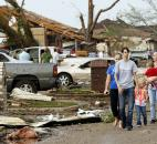 People walk through a neighborhood after a tornado struck south Oklahoma City and Moore, Okla., on Monday. (Photo by The Associated Press)