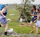 A parent rushes to embrace her child as a teacher escorts her away from Briarwood Elementary School after a tornado destroyed the school in south  Oklahoma City, Okla., on Monday. (Photo by The Associated Press)