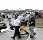 A tornado victim is wheels to an ambulance Monday. (Photo by The Associated Press)