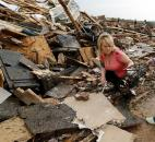 Sydney Whittaker salvages items from Trends Salon on Monday in Moore, Okla.  (Photo by The Associated Press)