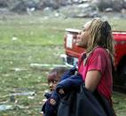 A woman carries an injured child to a triage center near the Plaza Towers Elementary School in Moore, Okla., on Monday. (Photo by The Associated Press)