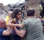 A child is pulled from the rubble of the Plaza Towers Elementary School in Moore, Okla., and passed along to rescuers  Monday. (Photo by The Associated Press)