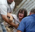 A child calls to his father after being pulled from the rubble of the Tower Plaza Elementary School after a tornado Monday in Moore, Okla. (Photo by The Associated Press)