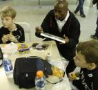 Clayton, 10, left, and Colin, 10, right, have lunch with DaMarcus Beasley as he autographs some pictures during a break in Tuesday's session of the Beasley National Soccer School holiday camp for children at The Plex South.
