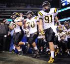 Snider's Ruben Holcomb, left, Sean Englert and Joshua Spitnale take to the field with the rest of the team before the start of their 5A state finals game against Lawrence Central.
