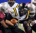 Snider's Alec Reuille, center, tries to gain some extra yards as he is tackled by Lawrence Central's Marcus Tipton, left, and Quenten Turman. Photo by Rob Edwards