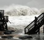 Huge waves break just off the beach Monday as Brandon Moncrief walks down the steps from an oceanfront motel in Buxton, N.C., on Hatteras Island.